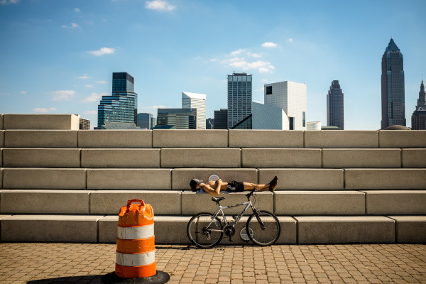 A biker takes a rest in the Voinovich Bicentennial Park at lake Erie, in front of a view of downtown Cleveland, OH. (2013)